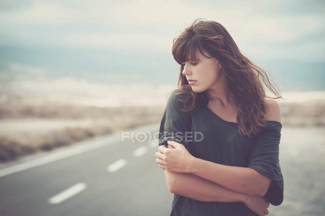 Sad young woman standing on road — Stock Photo