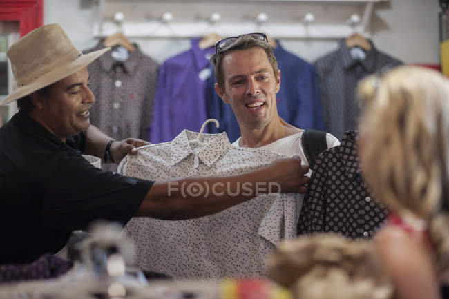 Cheerful friendly shopkeeper in shop helping clients — Stock Photo