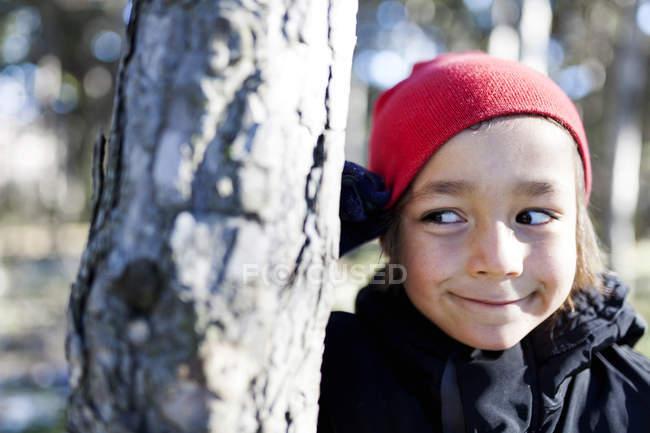 Retrato de um garotinho sorridente escondido atrás do tronco da árvore — Fotografia de Stock