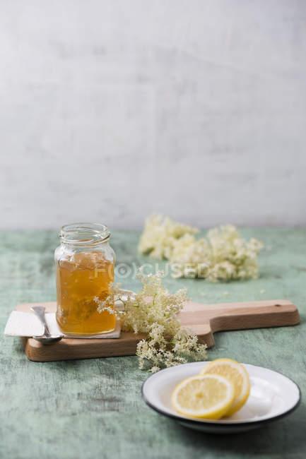 Стакан Элдерфлауэр желе с цветами на деревянной доске — стоковое фото