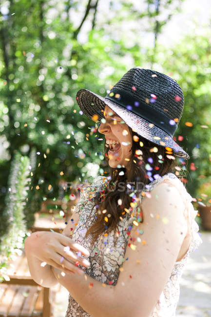 Enthusiastic young woman playing with confetti — Stock Photo