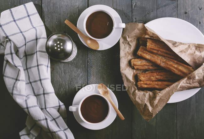Vue du dessus de Churros avec des tasses de chocolat chaud — Photo de stock