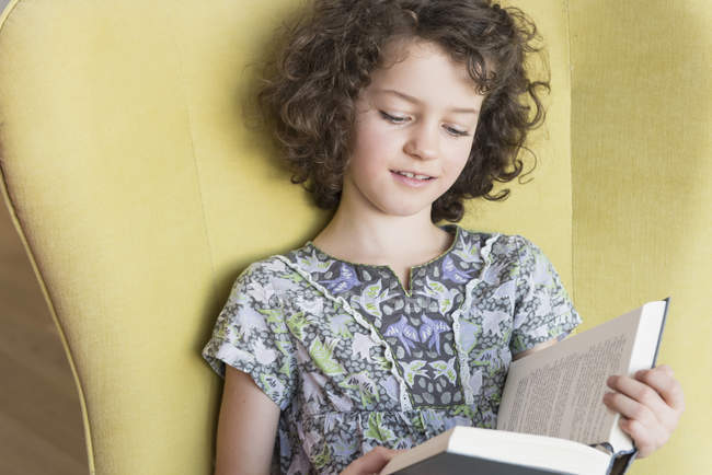 Cute curly girl reading book against yellow wall — Stock Photo