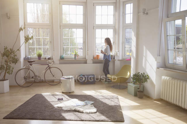 Женщина дома смотрит в окно — стоковое фото