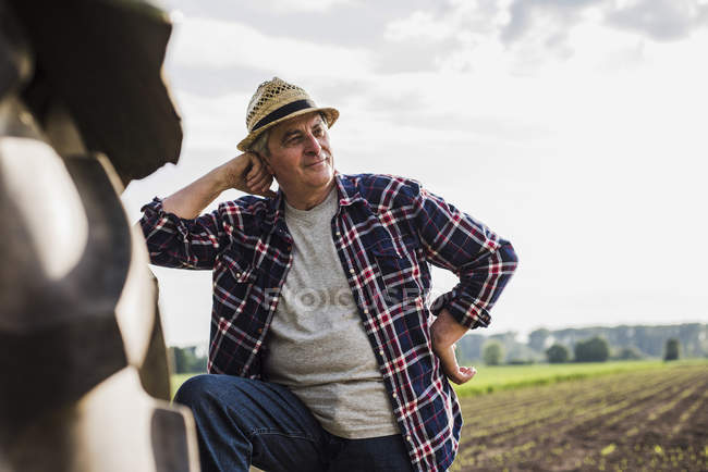 Farmer leaning on tractor at a field — Stock Photo