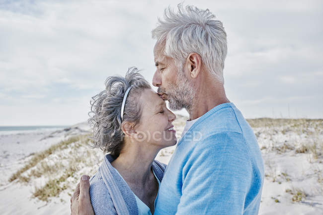 Happy couple kissing on the beach — Stock Photo
