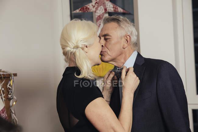 Älteres Paar küssen während der Befestigung Fliege für Silvester party — Stockfoto