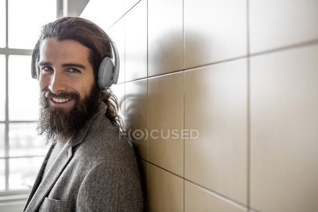 Young bearded man listening music with headphones and looking at camera — Stock Photo