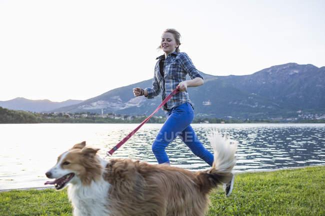Италия, Лекко, девочка-подросток бегает со своей собакой на берегу — стоковое фото