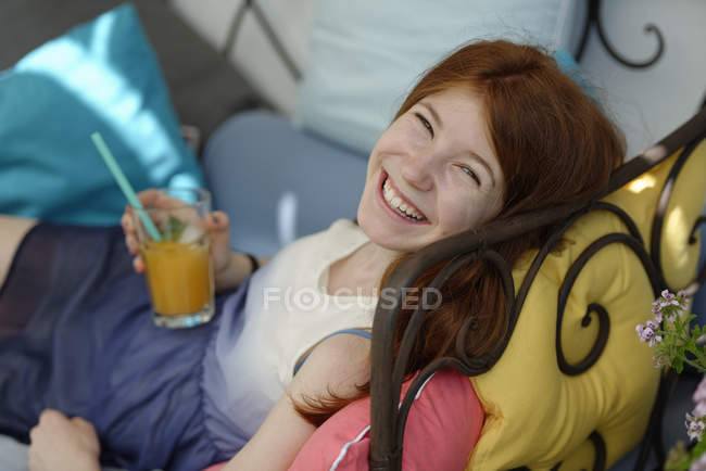 Portrait of happy teenage girl sitting on couch on the terrace with glass of juice — Stock Photo