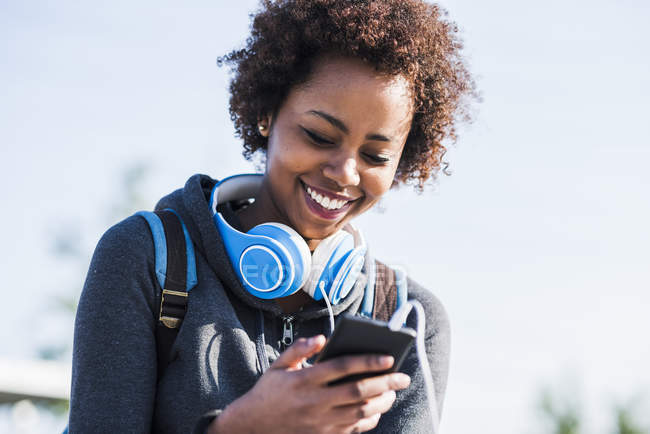 Smiling young woman wearing headphones looking at cell phone outdoors — Stock Photo