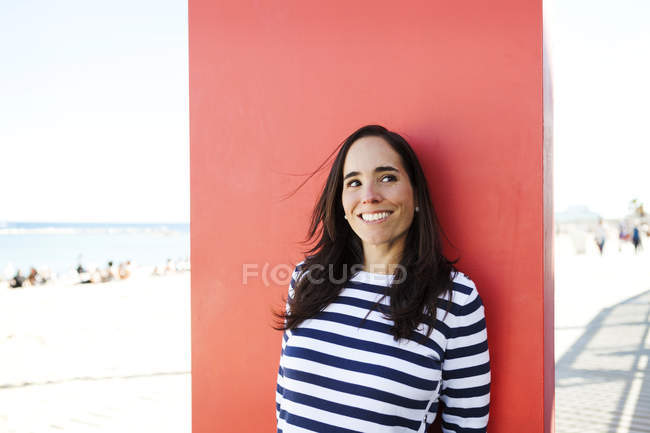 Portrait of woman wearing striped sweater leaning against red panel — Stock Photo