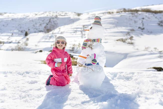 Carina ragazza caucasica che gioca con pupazzi di neve in inverno — Foto stock