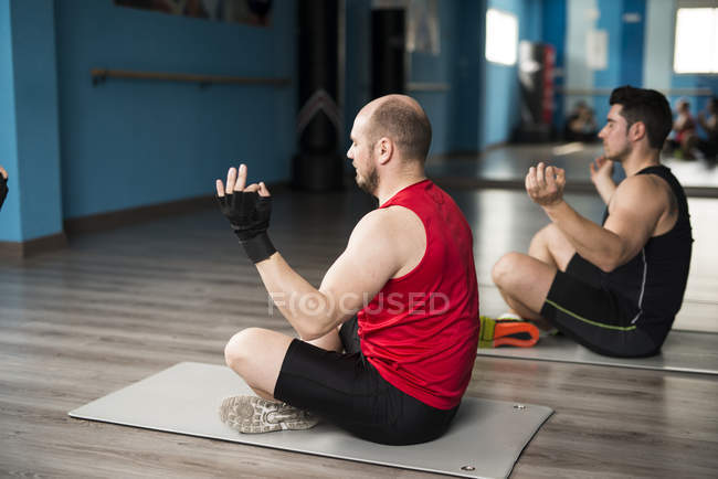 Two caucasian men meditating after yoga class — Stock Photo
