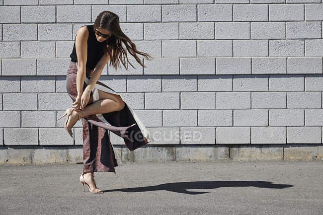Mulher jovem na moda na frente da parede de tijolo ajustando seu sapato — Fotografia de Stock