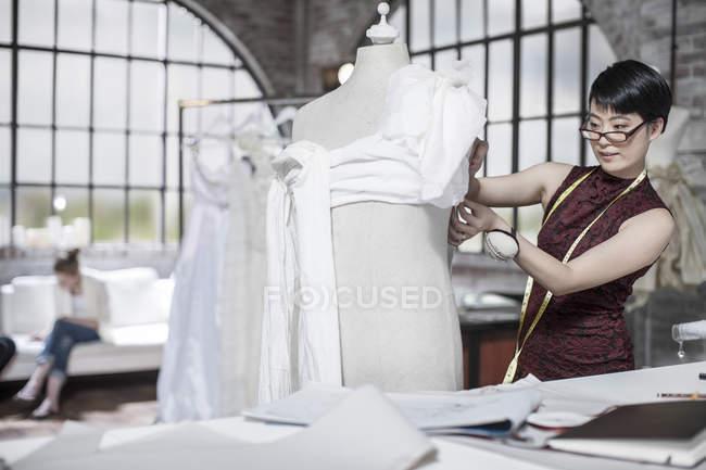 Дизайнер свадебных платьев работает в студии — стоковое фото