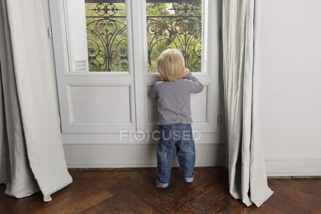 Rückansicht des Kleinkind Blick durch Fenster — Stockfoto