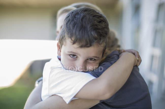 Ritratto di bambino triste che abbraccia sua madre a casa — Foto stock