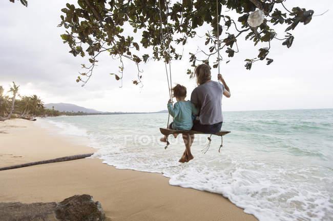Thailand, Familie sitzt auf Schaukel am Strand — Stockfoto