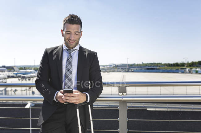 Businessman standing with luggage and cell phone — Stock Photo