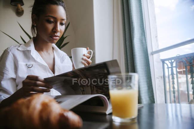 Портрет молодой женщины, читающей журнал за завтраком — стоковое фото