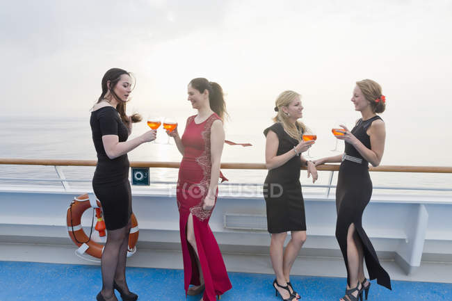 Four women with aperitives standing on deck of a cruise liner — Stock Photo