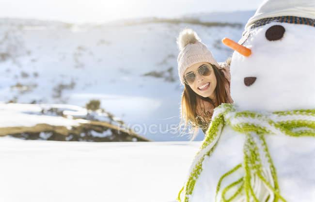 Счастливая молодая женщина со снеговиком — стоковое фото