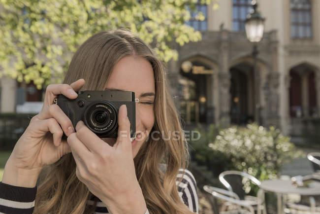 Sorridente giovane donna scattare una foto — Foto stock