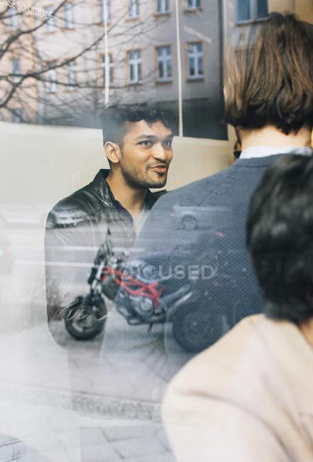 Homem por trás da vidraça conversando em um café — Fotografia de Stock