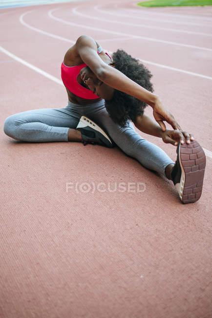 Jeune athlète noir qui s'étend devant la course dans le stade — Photo de stock