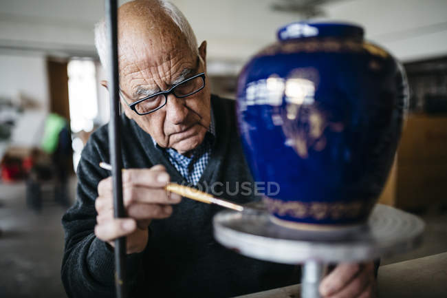 Senior man decorating ceramic vase in his spare time — Stock Photo