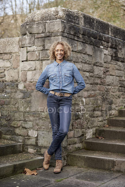 Portrait of smiling woman wearing denim shirt and jeans — Stock Photo