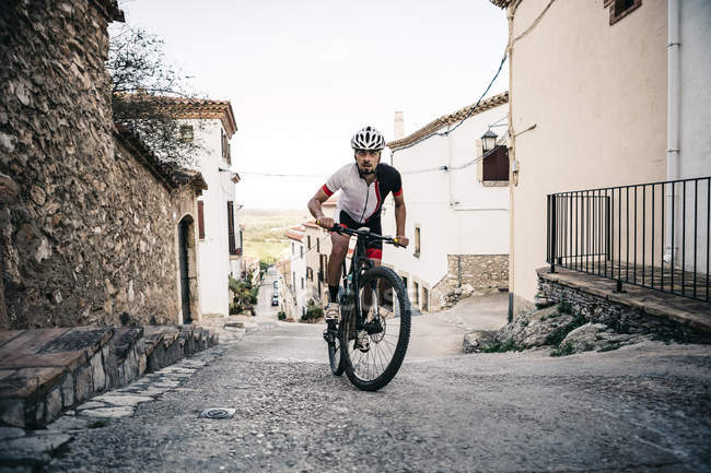 Mountain biker riding uphill in mountain village — Stock Photo