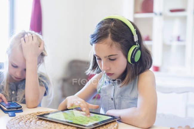 Две девушки с помощью мобильных устройств — стоковое фото