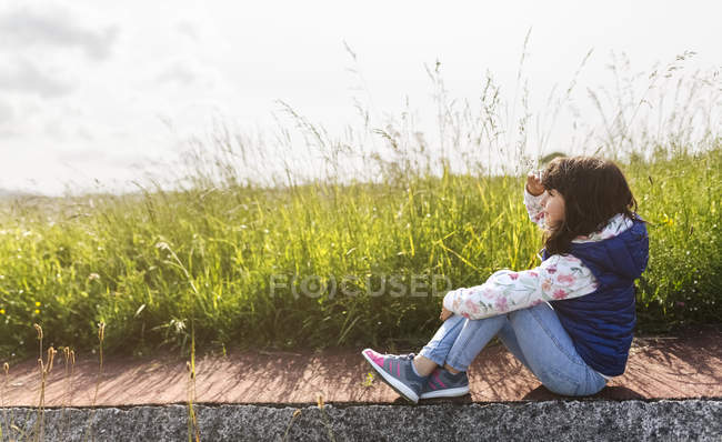 Little girl sitting on pavement in front of a meadow looking at distance — Stock Photo