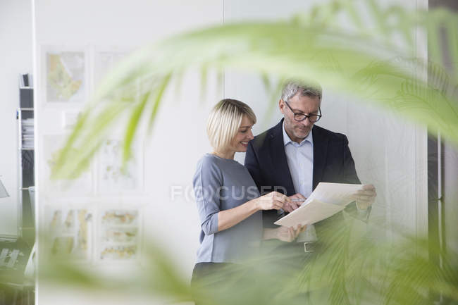 Businessman and businesswoman discussing documents in office — Stock Photo