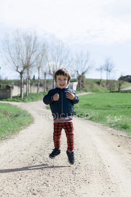 Ritratto di piccolo ragazzo felice che salta in aria — Foto stock