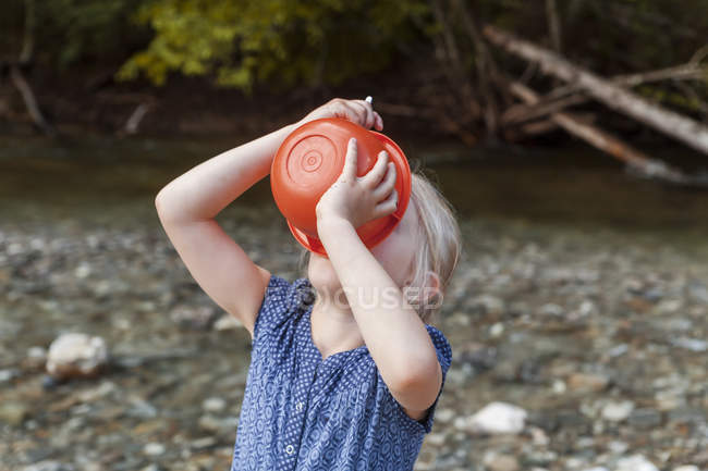 Chica rubia bebiendo de un tazón de plástico - foto de stock