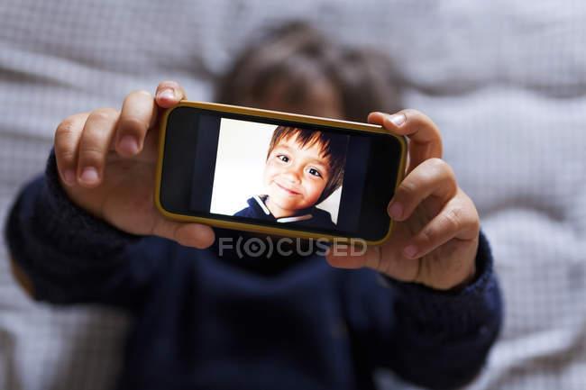 Menino, segurando um telefone celular com imagens de si mesmo — Fotografia de Stock