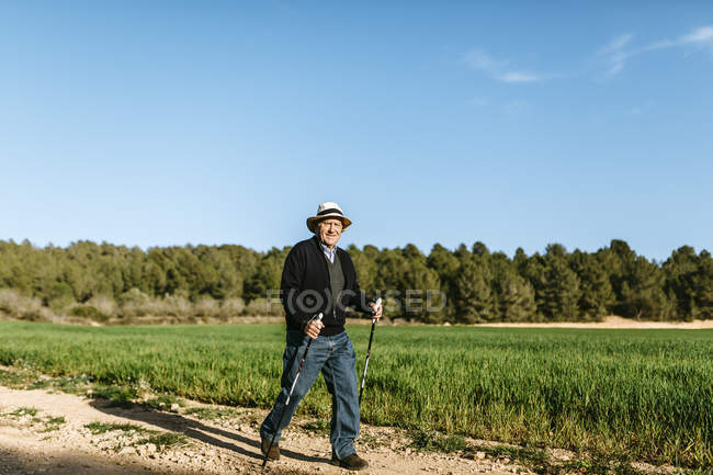 Homem sênior andando com paus no campo — Fotografia de Stock
