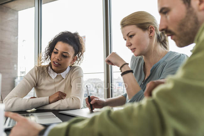 Three colleagues in office working together — Stock Photo