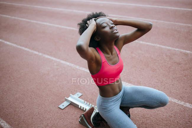 Подготовка к гонке на стадионе молодой спортсменка — стоковое фото
