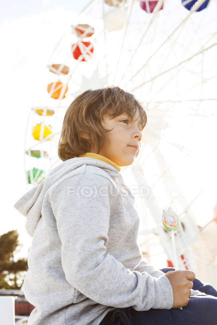Little boy with lollipop sitting in front of big wheel — Stock Photo