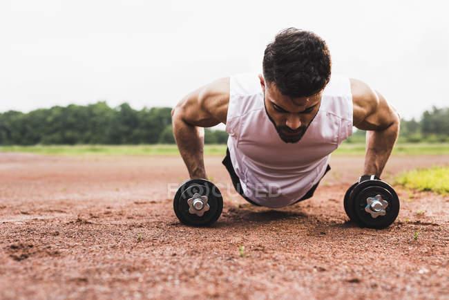 Спортсмен отжимается гантелями на спортивной площадке — стоковое фото