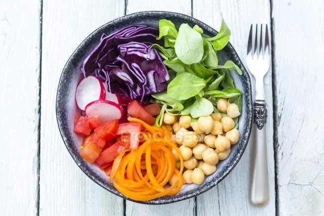 Веселка салат в миску з нут, помідори, морква, Червона капуста, Червона редиска, салату — стокове фото