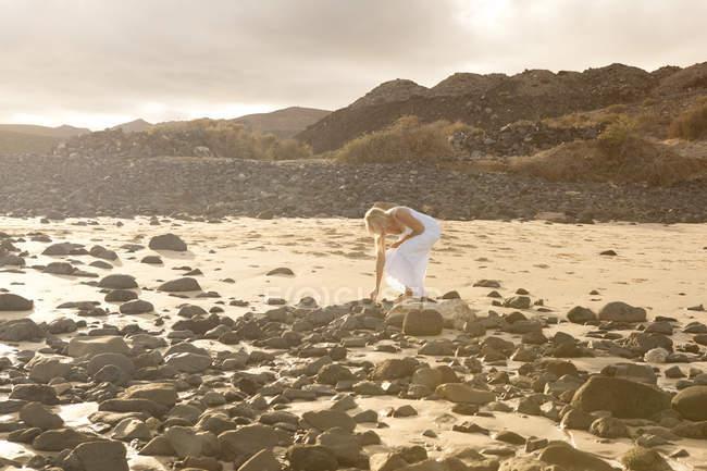 Испания, Фуэртевентура, Хандия, женщина на каменистом пляже — стоковое фото