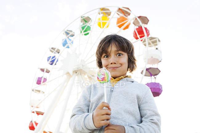 Retrato de menino com pirulito puxando caras engraçadas na frente da roda grande — Fotografia de Stock