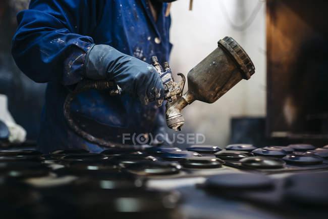 Cerámica de trabajador femenino de la pintura con pistola pulverizadora - foto de stock