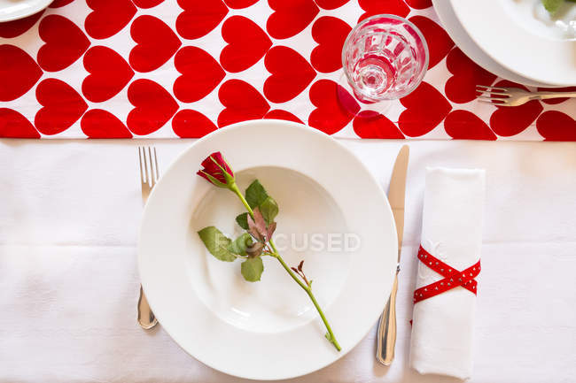 Laid table with heart shaped tablecloth and rose on bowl — Stock Photo