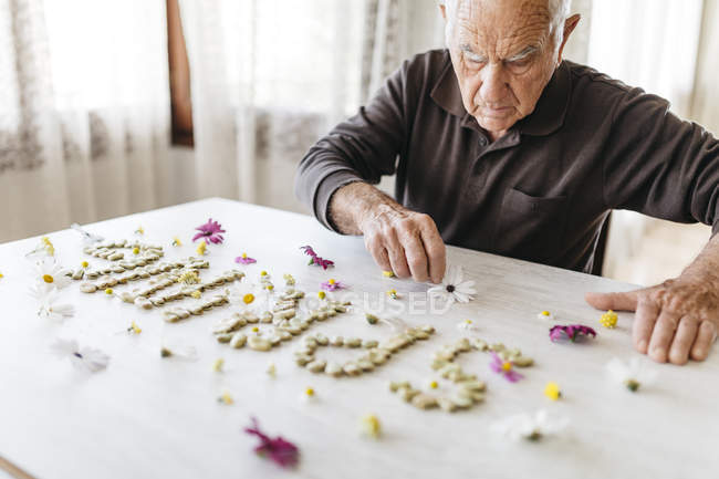 Senior man shaping the word 'spring' with dried beans surrounded by flowers on a table — Stock Photo